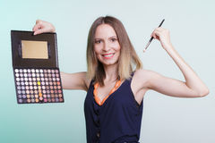 Woman applying eyeshadow with makeup palette. Royalty Free Stock Photo