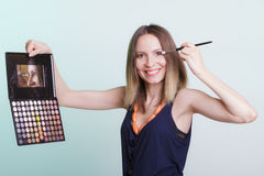 Woman applying eyeshadow with makeup palette. Stock Photography