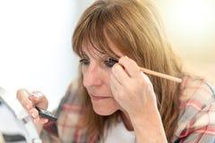 Woman applying eyeshadow powder, light effect Stock Photos