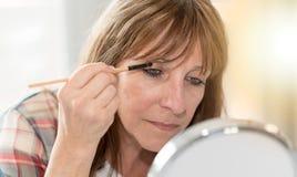 Woman applying eyeshadow powder, light effect Royalty Free Stock Photos