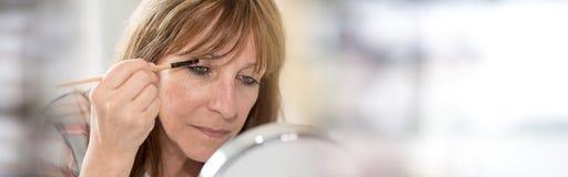 Woman applying eyeshadow powder. Mature woman applying eyeshadow powder royalty free stock images