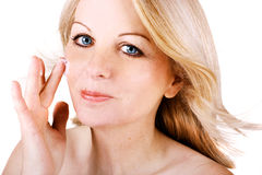 Woman applying face cream Stock Images