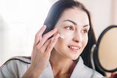 Woman applying face cream. Young attractive woman in white bathrobe applying face cream Royalty Free Stock Photography