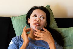 Woman applying face mask at home. Asian woman applying face mask at home royalty free stock photography
