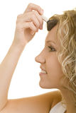 Woman applying face powder. Side portrait of young woman applying face powder to forehead, white background royalty free stock image