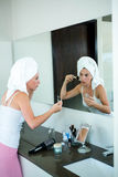 woman applying face powder in the bathroom mirror Stock Photos