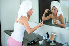 woman applying face powder in the bathroom mirror Stock Images