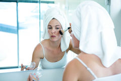 woman applying face powder in the bathroom mirror Royalty Free Stock Images