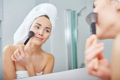 Woman applying face powder in the bathroom Royalty Free Stock Images