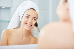 Woman applying face powder in the bathroom Royalty Free Stock Photos