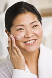 Woman Applying Facial Cream Stock Images
