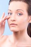 Woman is applying facial cream. Beautiful woman is applying facial cream, on blue background Stock Photos