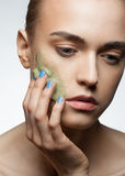 Woman applying facial scrub. Portrait of young beautiful woman applying facial scrub on her face Stock Images