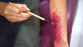 Woman applying fake wounds makeup on the arm