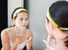 Woman applying foam cream to face reflect with bathroom mirror.  Stock Photo