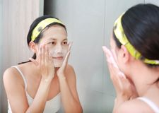 Woman applying foam cream to face reflect with bathroom mirror.  Royalty Free Stock Photography