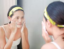 Woman applying foam cream to face reflect with bathroom mirror.  Royalty Free Stock Image