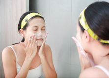 Woman applying foam cream to face reflect with bathroom mirror.  Stock Images