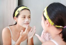 Woman applying foam cream to face reflect with bathroom mirror.  Royalty Free Stock Photo