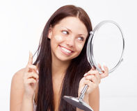 Woman applying foundation. Beautiful young brunette woman  applying  foundation and looking into the mirror at home Stock Images
