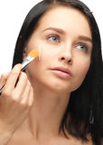 Woman applying foundation Stock Photography