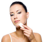 Woman applying foundation on face Stock Image