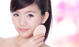 Woman applying foundation on face Royalty Free Stock Photo