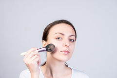 Woman Applying Foundation on Face Using a Brush Royalty Free Stock Image