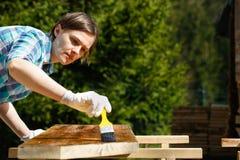 Woman applying fresh wood treatment paint Royalty Free Stock Photo
