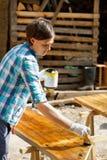 Woman applying fresh wood treatment paint Royalty Free Stock Photos