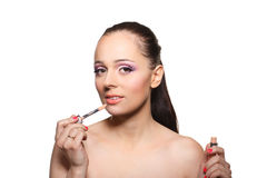 Woman applying gloss for lips. Royalty Free Stock Images