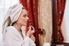 Woman applying gloss for lips. Royalty Free Stock Photo