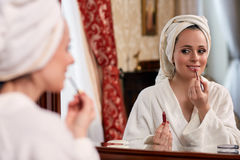 Woman applying gloss for lips. Young beautiful woman applying  gloss for lips sits before a house  dressing table Stock Photo