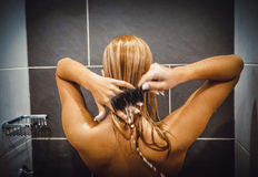 Woman applying hair conditioner. royalty free stock photography