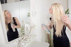 Woman applying hairspray to her hair Royalty Free Stock Photo