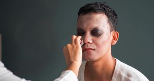 Woman applying halloween makeup on man face