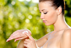 Woman applying on hand cosmetic cream Stock Photos