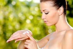Woman applying on hand cosmetic cream. Beautiful woman applying on hand cosmetic cream. Green natural background Stock Photos