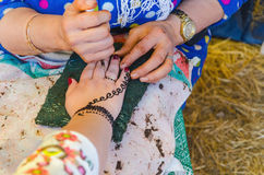 Woman applying henna tattoo Royalty Free Stock Images