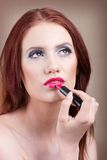 Woman is applying her lips with lipstick Royalty Free Stock Image