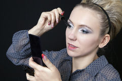 Woman applying her make-up Stock Images