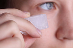 Woman applying ice cube to refresh her face skin near eyes. Beauty, skin care concept Royalty Free Stock Images