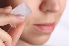 Woman applying ice cube to refresh her face skin near eyes. Beauty, skin care concept Stock Image