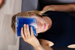 Woman Applying Ice Gel Pack On Forehead. Elevated View Of A Woman`s Hand Applying Ice Gel Pack On Forehead stock photo
