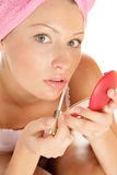 Woman applying lip gloss Stock Photography