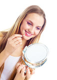 Woman applying lip gloss. Pretty young blond woman applying lip gloss Stock Image