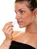 Woman applying lip gloss Royalty Free Stock Photos