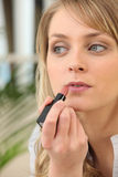 Woman applying lip gloss Stock Images
