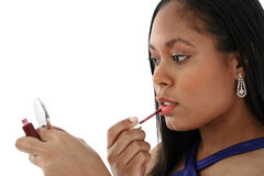 Woman applying lip gloss. A young woman applying lip gloss with a brush while looking at her reflection in a pocket mirror Stock Image