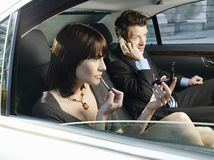 Woman Applying Lip Gloss And Man Using Mobile Phone In Car Stock Photography